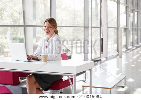 Businesswoman with laptop smiling and looking to camera