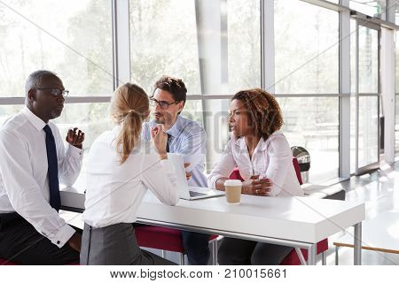 Young business people talking over coffee in a modern lobby