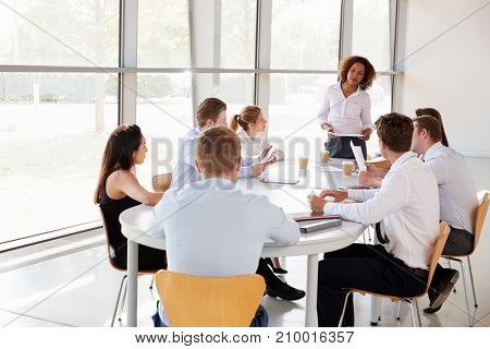 Businesswoman stands holding documents at a team meeting