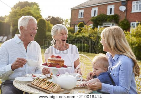 Grandparents Have Afternoon Tea With Grandson And Adult Daughter