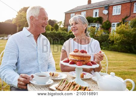 Retired Couple Enjoying Afternoon Tea In Garden At Home