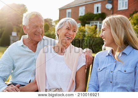 Senior Parents Sitting On Seat In Garden With Adult Daughter