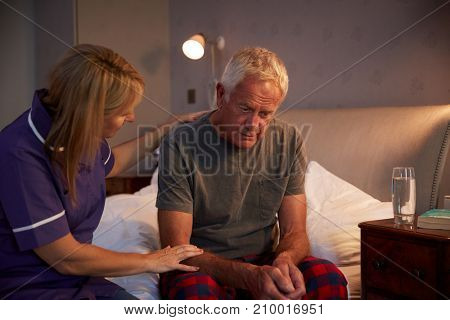 Nurse Making Home Visit To Senior Man Suffering With Depression