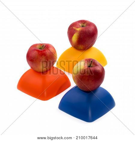 Three ripe red apples on a yellow red and blue figure