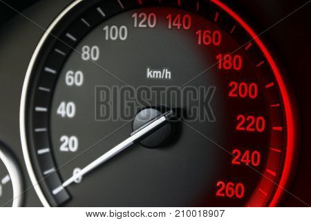 Car instrument panel dashboard closeup with visible speedometer car interior details with red signs