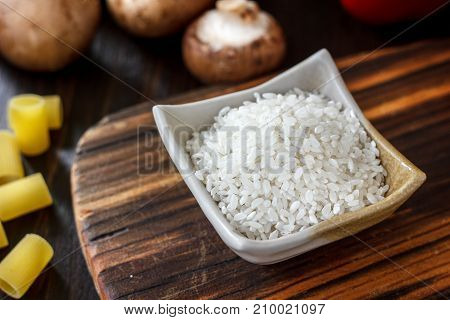 Ceramic bowl with the rice on wooden board