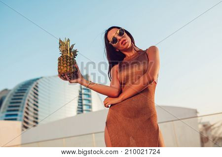 Attractive woman is standing with a pineapple cocktail in her hand.