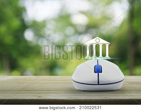 Bank icon with wireless computer mouse on wooden table over blur green tree in park Business banking online concept