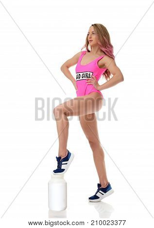 Beautiful caucasian female athlete with big protein can in pink body. Young woman in sportswear on white background