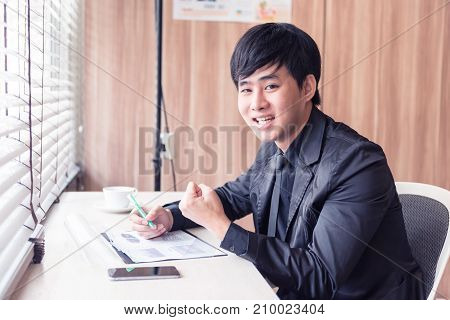 successful businessman working on documents graphic concentrated with mobile phone on the table at office.