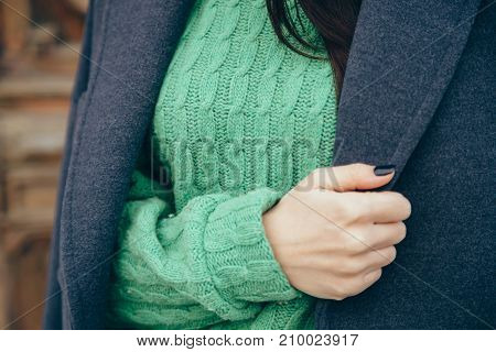 Details of women's clothing. Close-up hand of a woman in a sweater and coat.