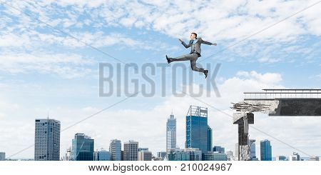 Businessman jumping over huge gap in concrete bridge as symbol of overcoming challenges. Cityscape on background. 3D rendering.