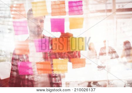 Stocks and shares against photo editor looking at multi colored sticky notes on glass