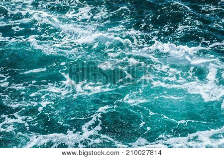 Azure foamy surface of the sea. Marine textured background.