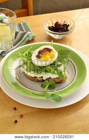 Toast with cream cheese arugula and boiled egg healthy breakfast, vertical