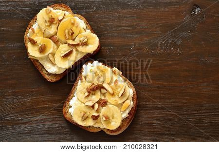 Toast with cream cheese topped with banana almonds and honey, top view, copy space