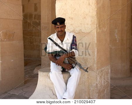 Luxor Egypt, August 2006: Policeman with rifle for tourist protection sitting on ruins of Luxor Temple in Egypt