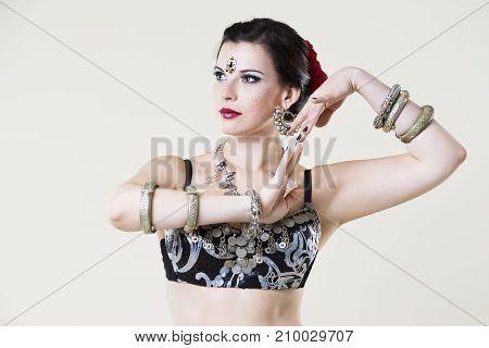 Women performs belly dance in ethnic dress on beige background studio shot