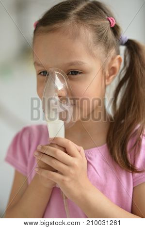 Portrait of a lovely little girl with inhaler