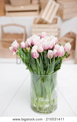 Beautiful light rosy tulips in glass vase on white table, close up. Variety of defocused wooden boxes on background. Floristics, arranging flowers for presents and decoration concept