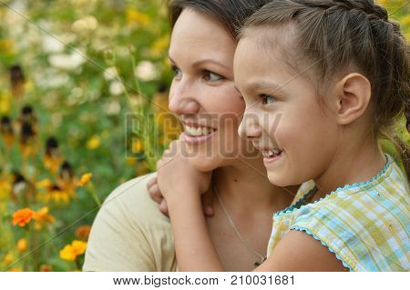 Portrait of mother and daughter hugging  outdoors