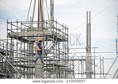 Working at height equipment. Fall arrestor device for worker with hooks for safety body harness on selective focus. Worker as a background.
