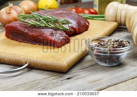 A Piece Of Raw Meat, Rosemary And Spices On The Kitchen Table