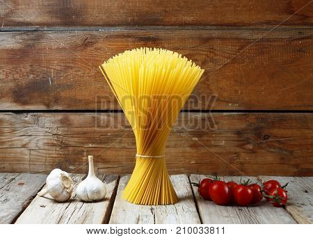 A Bunch Of Italian Spaghetti, Garlic, And Cherry Tomatoes On A Wooden Background. Concept: Tradition