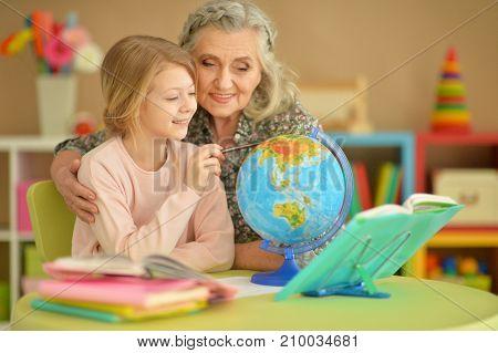 Portrait of a grandmother and granddaughter doing homework together