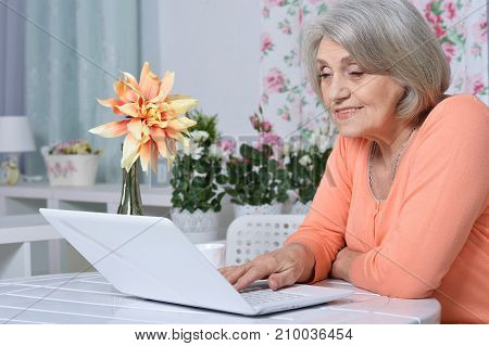 senior woman sitting at table with laptop