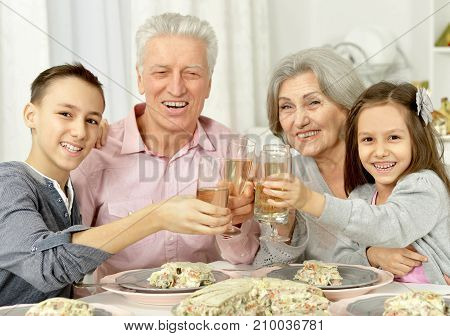 Grandparents and grandsons sitting at table and clanging glasses