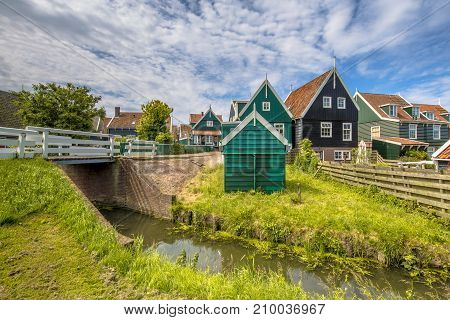 Characteristic Dutch Village Scene With Wooden Houses And Bridge Over Canal