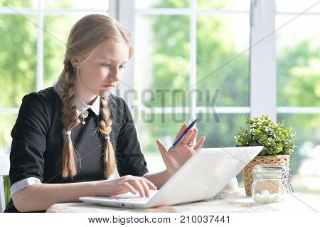 Teen girl using modern laptop while sitting at table