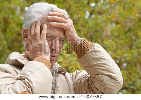 Senior man with headache holding hands on head