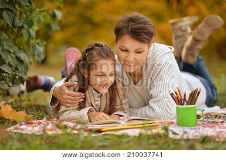 Little cute girl with her mother  reading book in  park