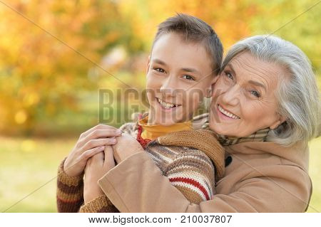Portrait of a grandmother and grandson hugging in park