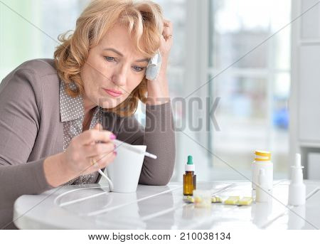 portrait of Sick mature woman with thermometer