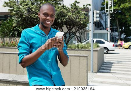 African american man using 4g with mobile phone in the summer in the city