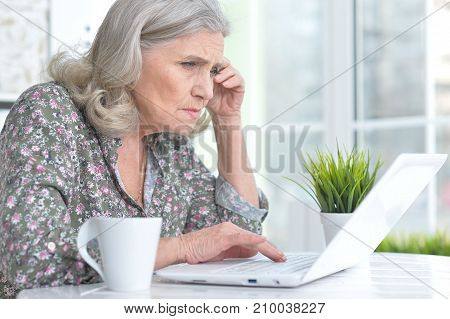 Sad senior woman sitting at table with laptop