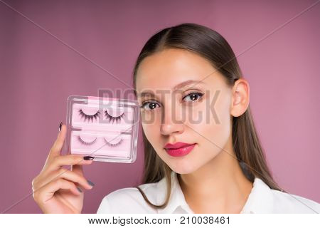 young beautiful girl holding a package with black false eyelashes in her hands