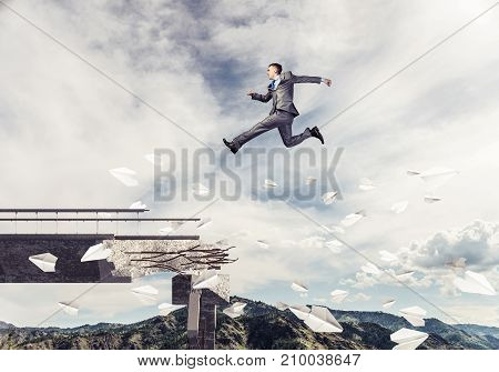 Businessman jumping over gap in bridge among flying paper planes as symbol of overcoming challenges. Skyscape and nature view on background. 3D rendering.
