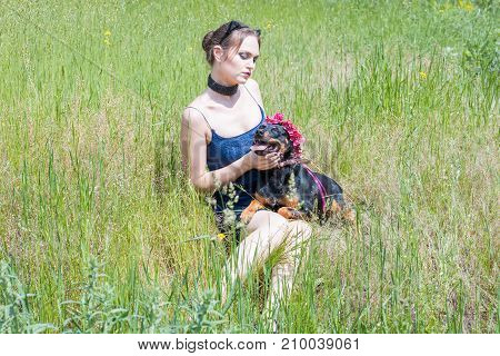 Girl and dog are sitting on the grass in the field