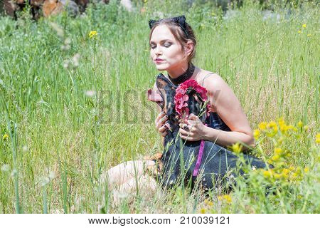 Beautiful girl and dog are sitting on the grass in the field