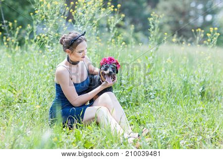 Portrait of a beautiful girl and a dog in the grass in the field