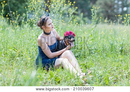 Portrait of a beautiful girl with a dog in the grass in the field