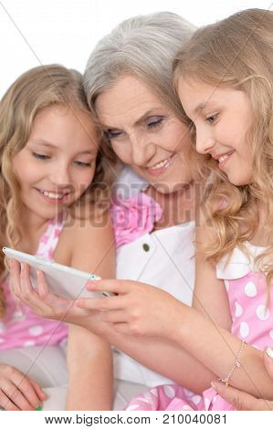 granny with her granddaughters using smartphone, close up