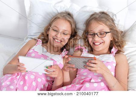 two sisters twins using smartphones, wearing eyeglasses