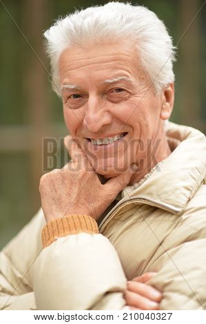 Outdoors portrait of smiling senior man holding hand on chin