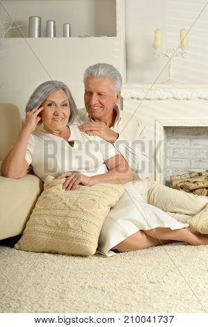 Senior couple sitting on floor near beige couch
