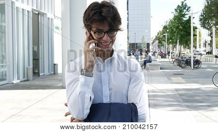 Handsome young businessman in city talking on cell phone, also looking at camera, serious